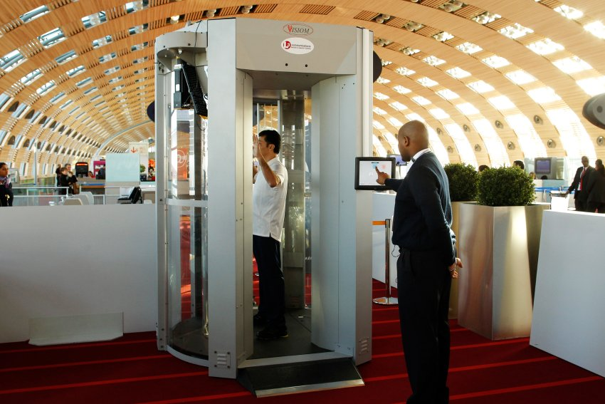 22 Feb 2010, ROISSY, France --- A security official (R) prepares to scan a man posing inside a full-body scanner being trialled by Roissy Charles-de-Gaulle airport during a photocall at the departure gate in Roissy near Paris February 22, 2010. France will use body scanners at some of its airports, initially to search passengers heading to the United States. REUTERS/Benoit Tessier (FRANCE - Tags: TRAVEL TRANSPORT CRIME LAW) --- Image by © BENOIT TESSIER/Reuters/Corbis