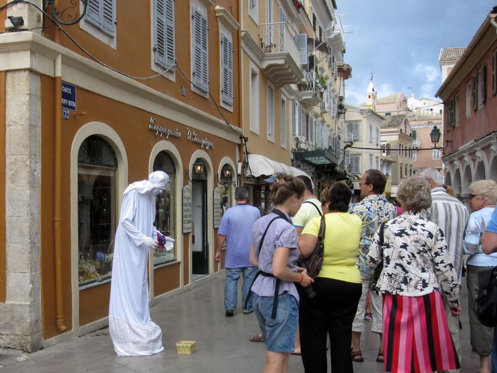 """Современный """"нищий"""" стоит у храма на острове Корфу (Греция)."""