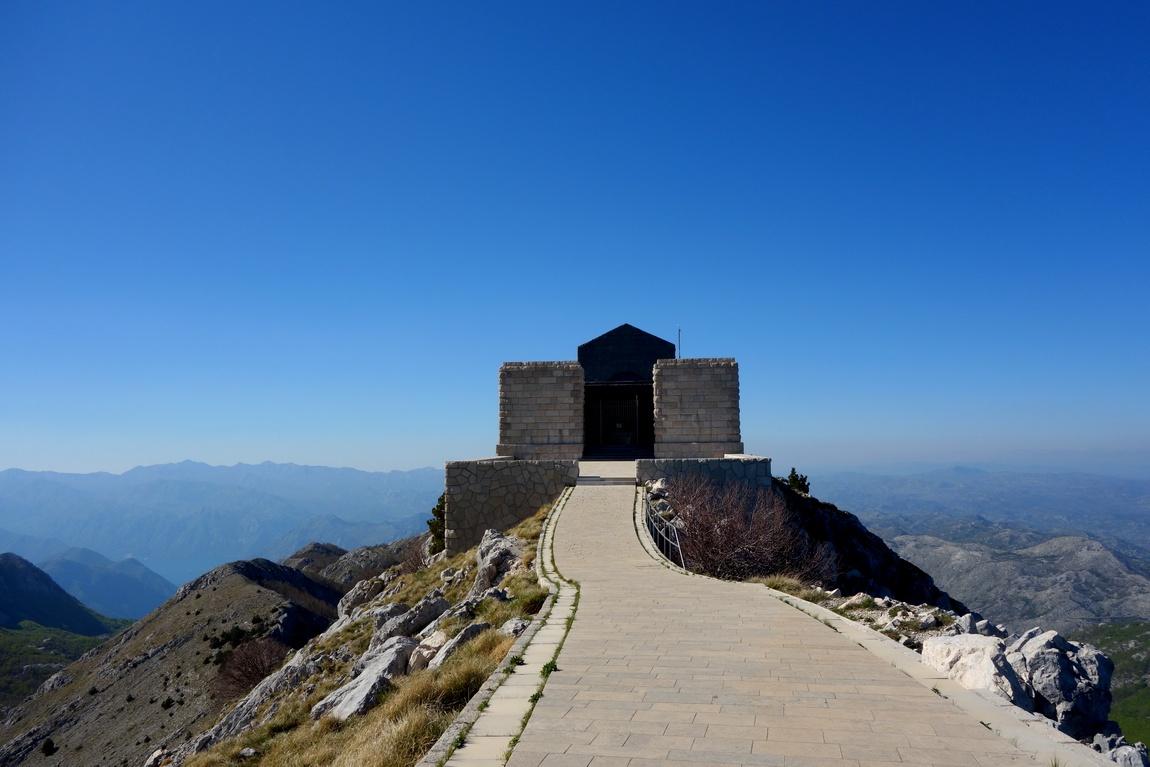 Вдали мавзолей Негоша на вершине горы Ловчен в Черногории